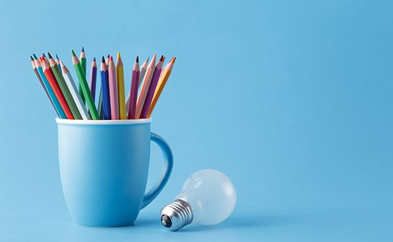 mug filled with color pencils and a light bulb next to it solid blue background
